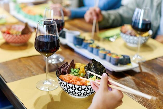 Persona che si gode una ciotola di poke o pesce crudo condito marinato con un bicchiere di vino rosso in un ristorante con gli amici in un primo piano sul cibo