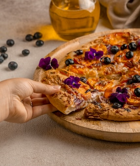 Persona che afferra una fetta di pizza con petali di fiori e mirtilli