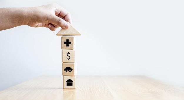 Una persona afferra un blocco di legno a forma di tetto triangolare sopra un blocco di legno rettangolare con icone di assistenza infermieristica, denaro, auto e casa. concetto di assicurazione. sfondo banner panoramico con spazio di copia.