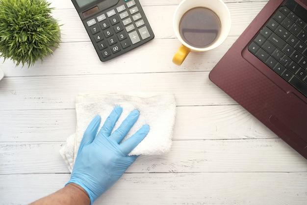 Persona mano in guanti monouso pulire la superficie del tavolo