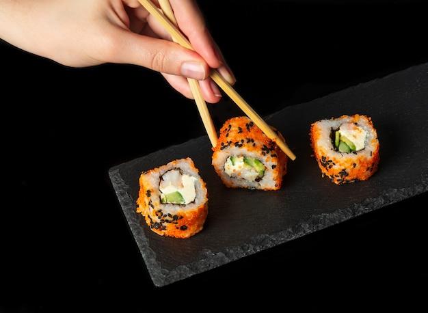 La mano della persona prende il rotolo di sushi con i bastoncini sushi di cibo tradizionale asiatico