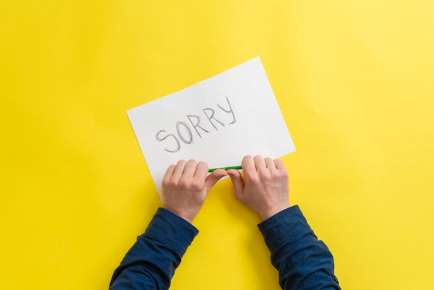 Una persona tiene in mano un foglio di carta con la parola scusa