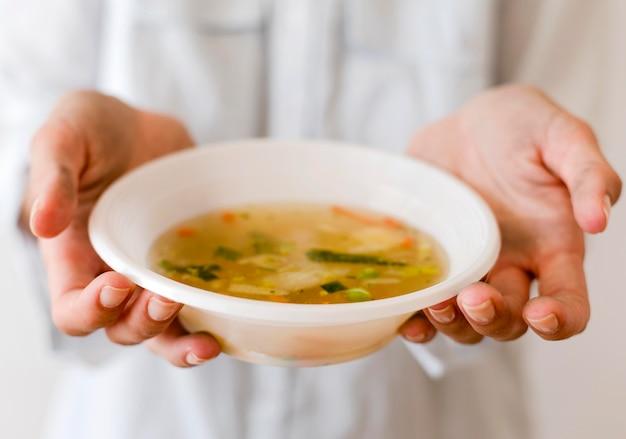 Persona che tiene la ciotola di zuppa per il giorno dell'alimento