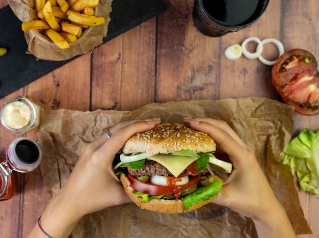 Persona in possesso di un hamburger con patatine fritte, anelli di cipolla e pomodoro sulla tavola di legno