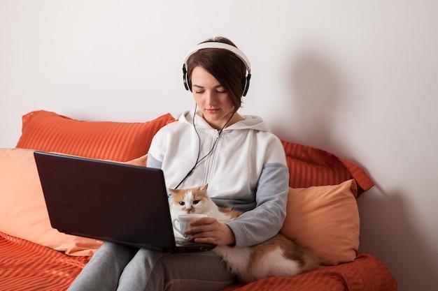 Una persona che tiene un gatto e un computer portatile. una scuola domestica e lavorare a casa