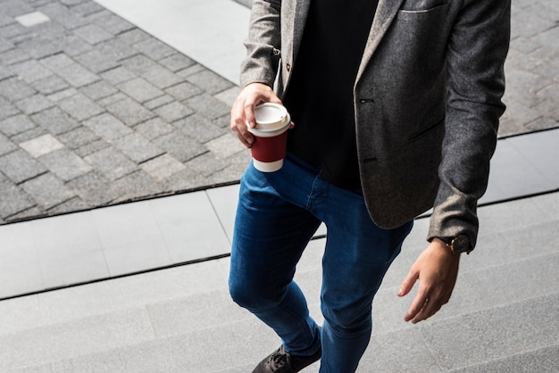 Persona in possesso di tazza di caffè caldo