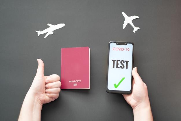 Persona in possesso di passaporto e smartphone con test covid su sfondo nero con aerei