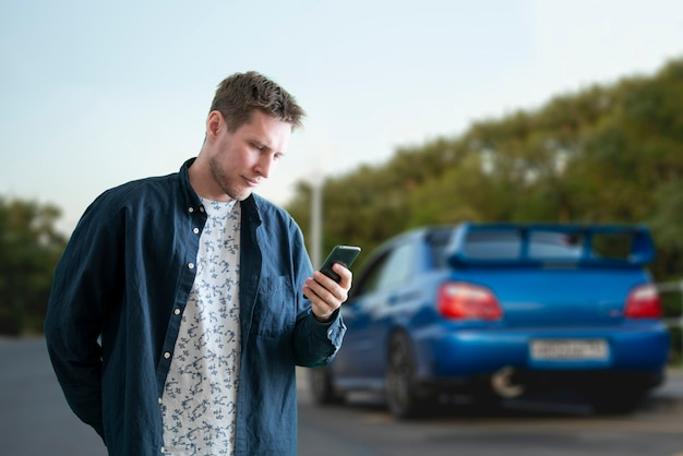 Una persona che tiene in mano uno smartphone e carica la batteria dell'auto elettrica