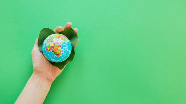 Persona in possesso di un piccolo globo con spazio di copia