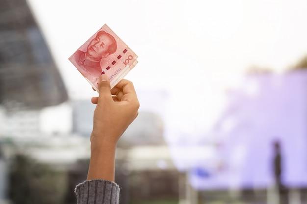 Persona in possesso di banconote yuan su una mano