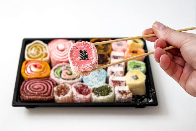 La persona tiene un pezzo di set di caramelle di gelatina multicolori con le bacchette