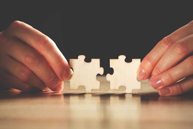 La persona tiene due pezzi del puzzle con le dita.