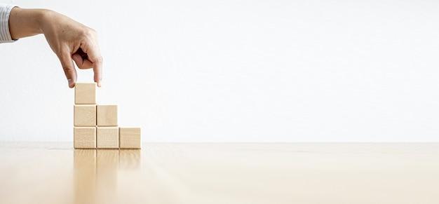 Una persona prende un blocco di legno e lo mette sopra. un blocco di legno con spazio per copiare testo o simboli viene utilizzato per creare banner. sfondo banner panoramico con spazio di copia.
