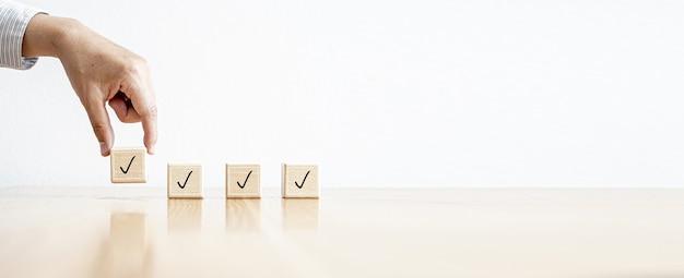 La persona sta raccogliendo quattro blocchi di legno rettangolari con delle icone posizionate su di essi. concetto di lista di controllo. sfondo banner con spazio di copia.
