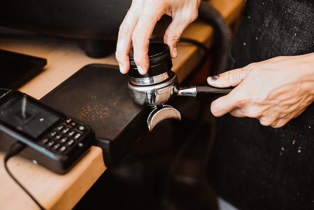 Persona che prepara il caffè fresco con la macchina della carruba?