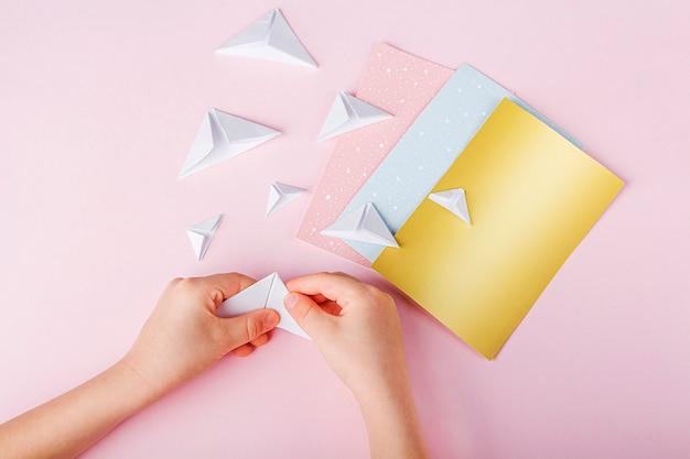 Persona che fa origami con carte colorate