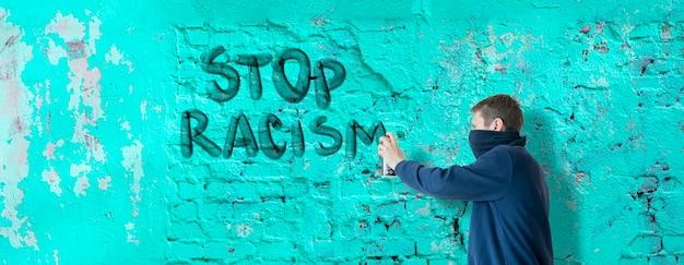 Una persona maschio scrive con vernice spray può fermare nessuna dichiarazione di razzismo sul muro, concetto di simbolo di graffiti