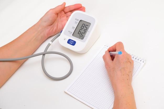 La persona misura la pressione sanguigna e annota le letture su un taccuino, sfondo bianco. mano e tonometro da vicino.