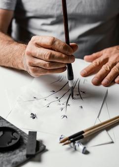Persona che dipinge con inchiostro cinese su carta bianca