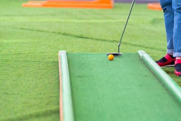 Persona che gioca una partita di minigolf su erba artificiale verde