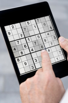 Persona che gioca a sudoku su un tablet