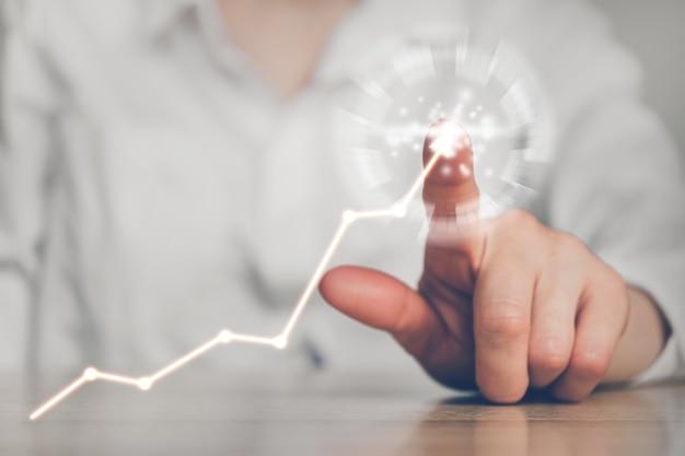 La persona punta il dito contro un grafico di crescita aziendale.