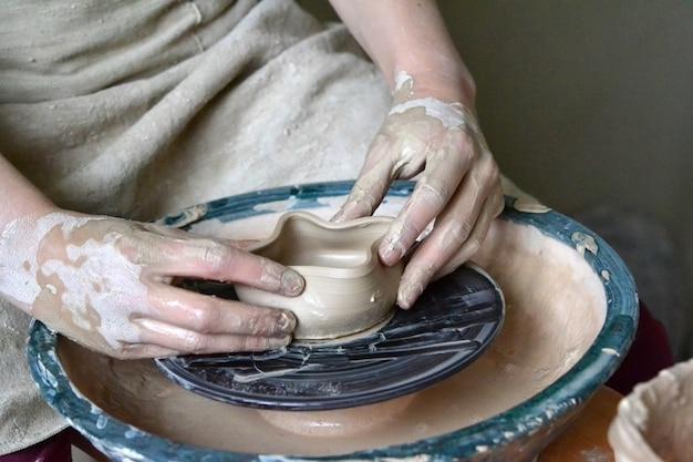 Persona vasaio fa vaso di terracotta su un tornio da vasaio