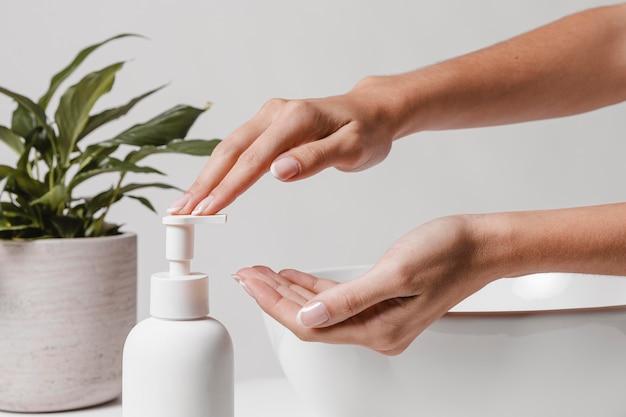 Persona che versa sapone in vista laterale della mano
