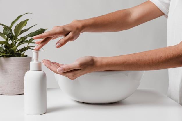 Persona che versa sapone in mano