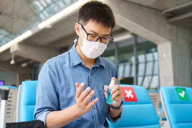 La persona nella mascherina protettiva disinfetta la sua mano