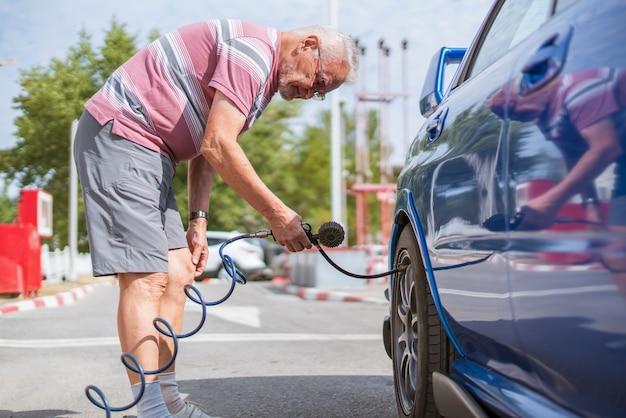Una persona pompa i pneumatici delle ruote dell'auto con un compressore con manometro