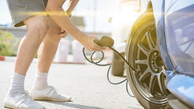 Una persona gonfia i pneumatici delle ruote dell'auto con un compressore con manometro
