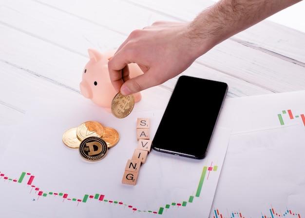 Persona che mette bitcoin d'oro nel salvadanaio su una scrivania e altri bitcoin, telefono, orari e salvataggio del titolo