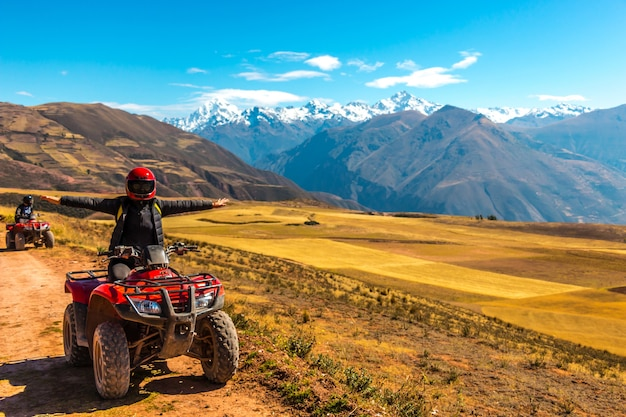 Una persona su un quad rosso che guarda a una bella vista e alza le mani