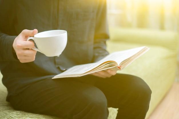 Una persona che si rilassa a casa, legge un libro e beve il tè, riposandosi la sera