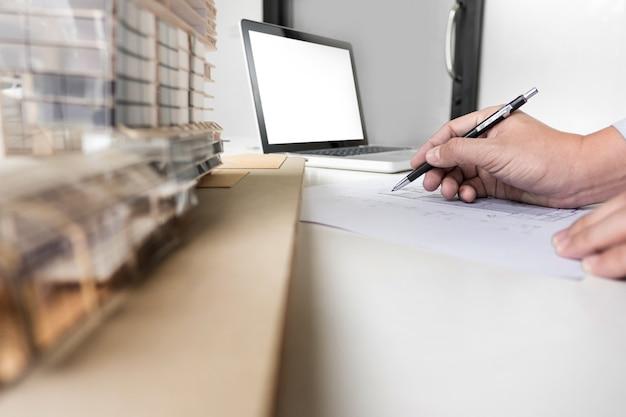 Ingegnere della persona piano di disegno della mano su stampa blu con attrezzature di architetto