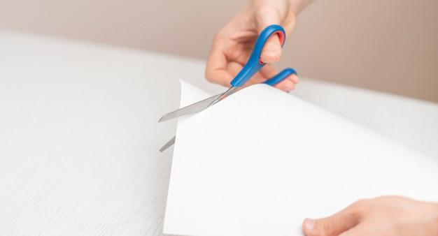 Le mani di una persona che tengono un foglio di carta e lo tagliano con le forbici