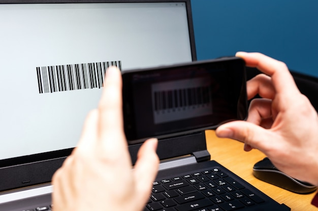 Scansione di persona con cellulare, codice a barre sullo schermo di un computer, pagamento moderno online con smartphone con app di scansione