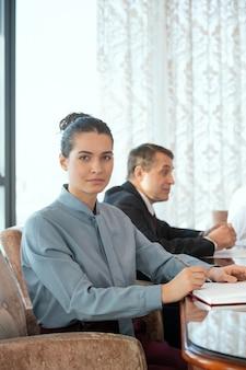 Una persona seduta in poltrona sullo sfondo del delegato che ha negoziato