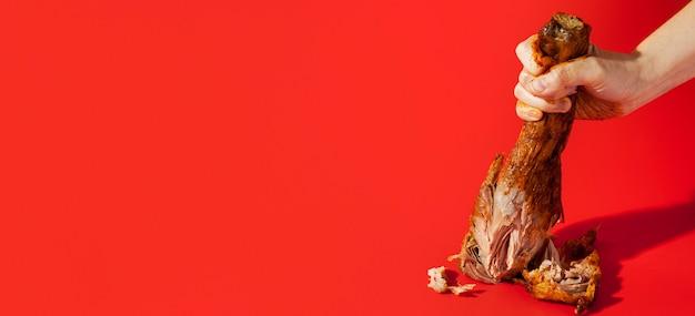 Persona che fracassa uno spazio della copia della coscia di pollo