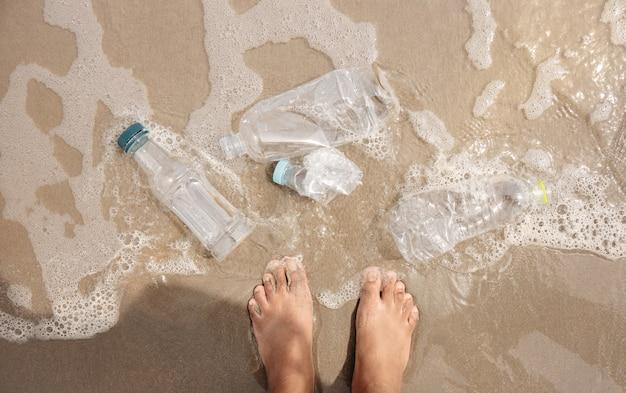 Persona in piedi con rifiuti di bottiglia di plastica sulla spiaggia