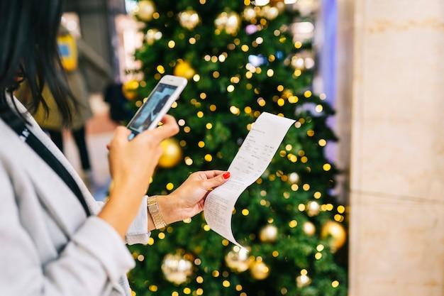 Una persona scatta una foto di un biglietto con il suo telefono con un albero di natale