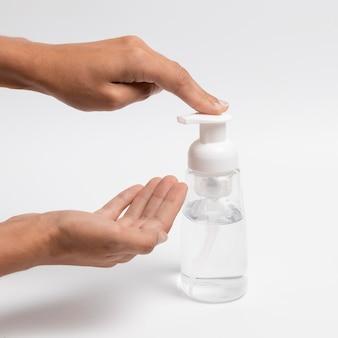 Persona che utilizza un disinfettante per le mani per la protezione