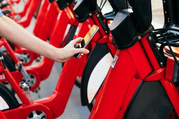 Persona che utilizza il telefono per eseguire la scansione del codice qr per noleggiare una bicicletta