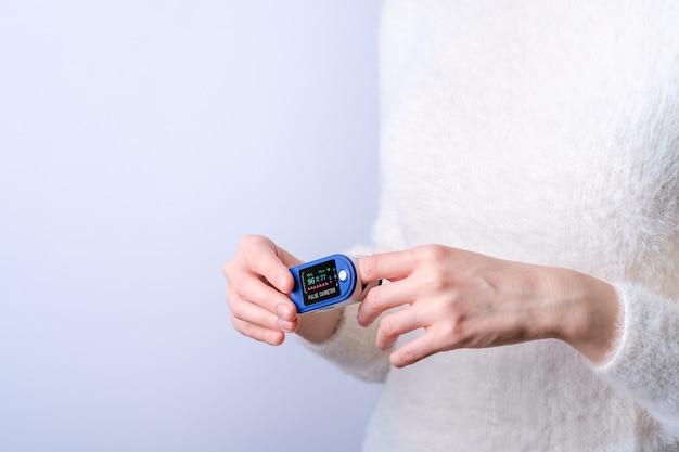 Persona che utilizza il dispositivo pulsossimetro sul dito, concetto di monitoraggio sanitario