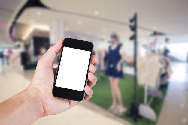 Persona che utilizza smartphone supporto schermo bianco a portata di mano con sfondo sfocato di negozio di abbigliamento.