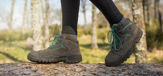 Persona che cammina attraverso la foresta in natura primo piano degli stivali