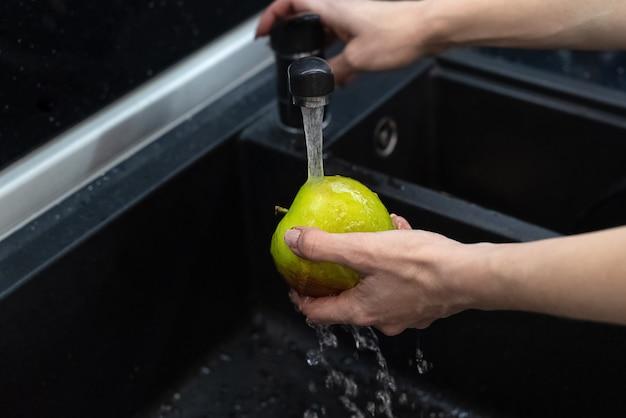 La persona lava la mela sotto l'acqua corrente nel lavello della cucina