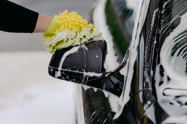 La persona lava l'auto con un panno alla stazione dell'auto
