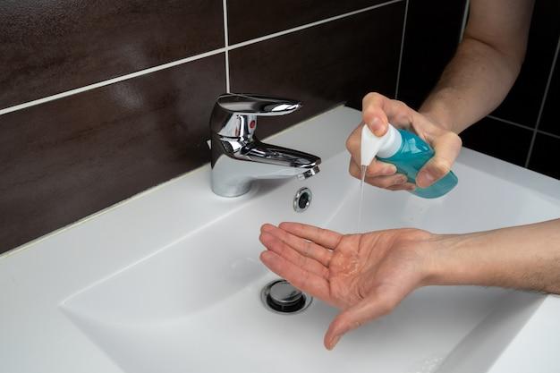 Persona che si lava le mani con disinfettante per le mani e gel alcolico in un gabinetto del bagno a causa del coronavirus covid-19